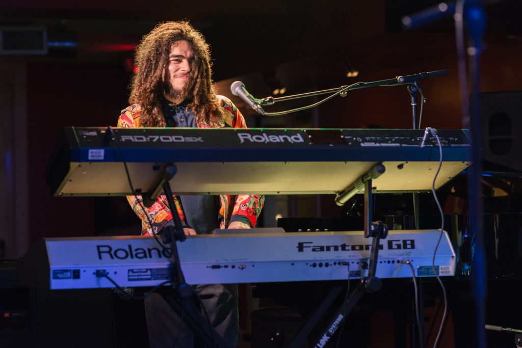 Musician plays the keyboard on stage.