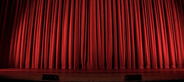 A lit theater stage with a red curtain