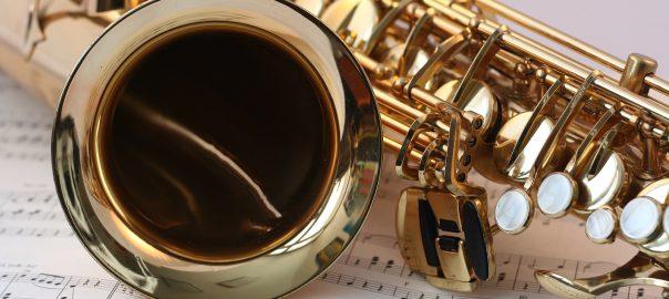A saxophone lying sideways on a sheet of music.