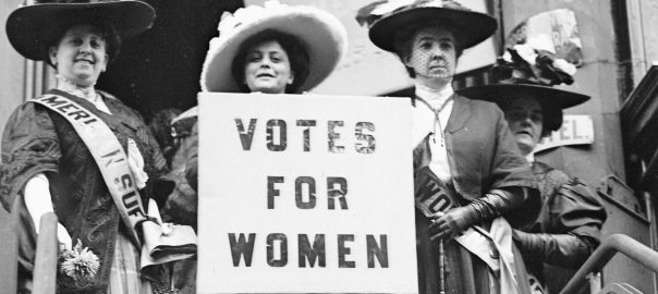 Suffragettes from the early 1900s hold up a sign reading votes for women