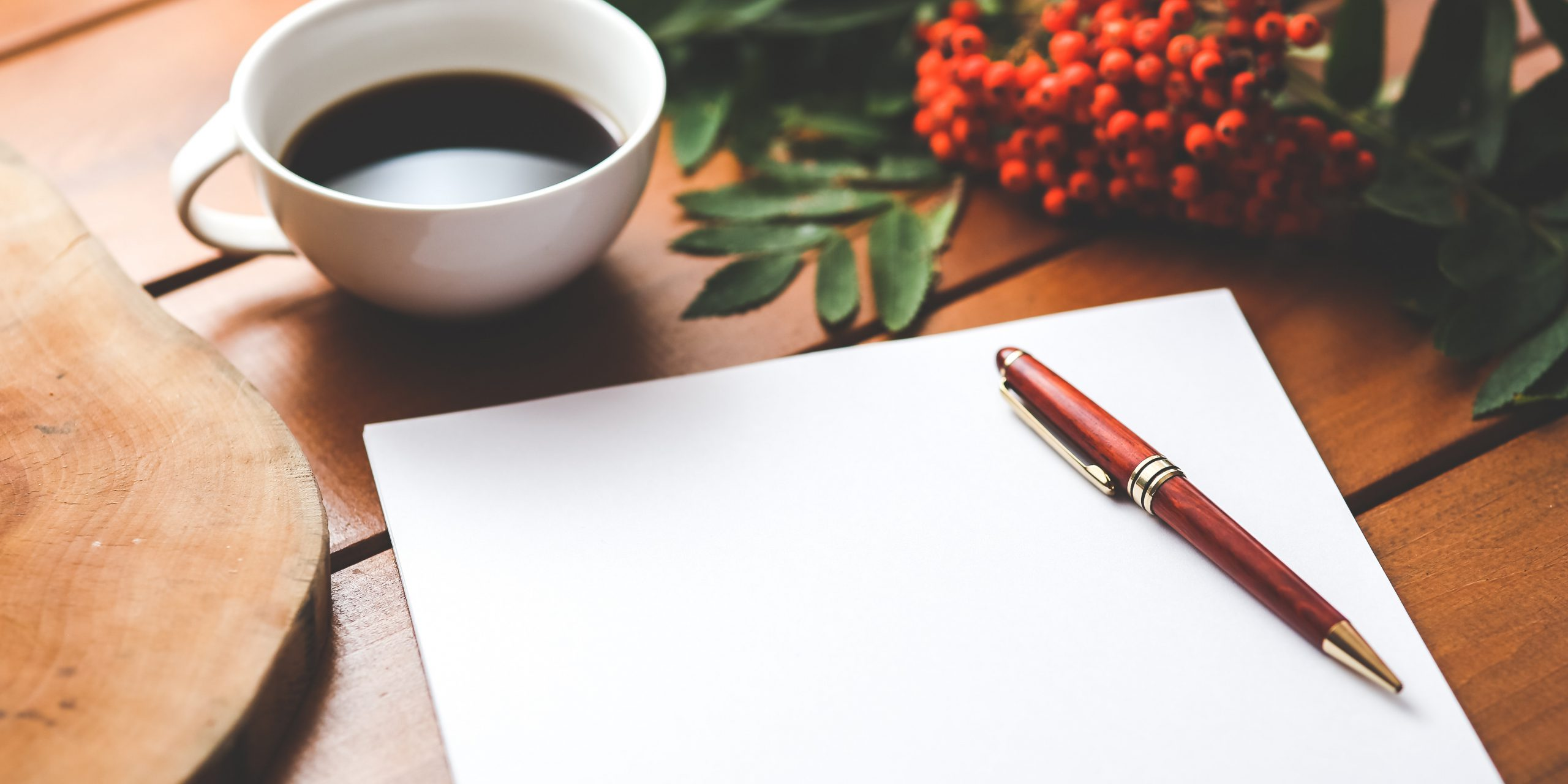 a red pen on a blank sheet of paper on a wooden desk