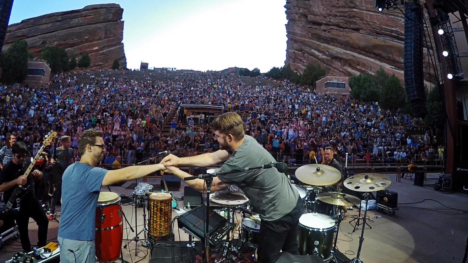 Hernly and Poynter shake hands over a drum set in front of a crowd of thousands at Red Rocks Amphitheater
