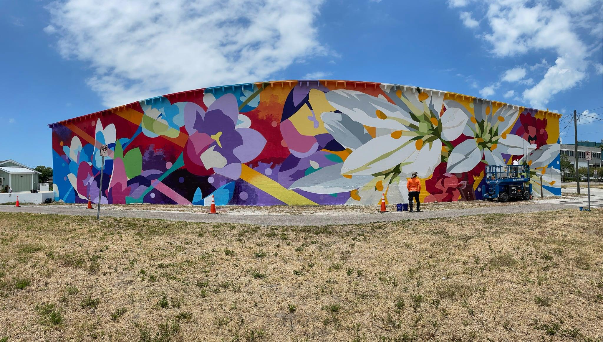 a colorful floral mural adorns the side of a building under a blue, lightly cloudy sky