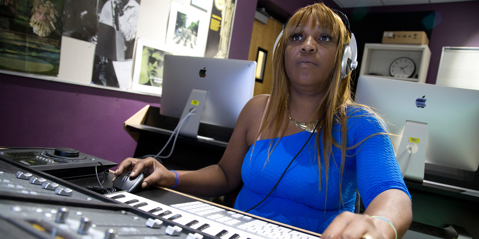 woman in blue shirt works behind a sound board doing audio production and engineering