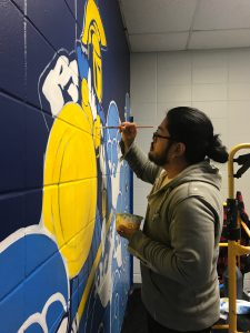 Man paints a mural of the St. Petersburg College mascot.