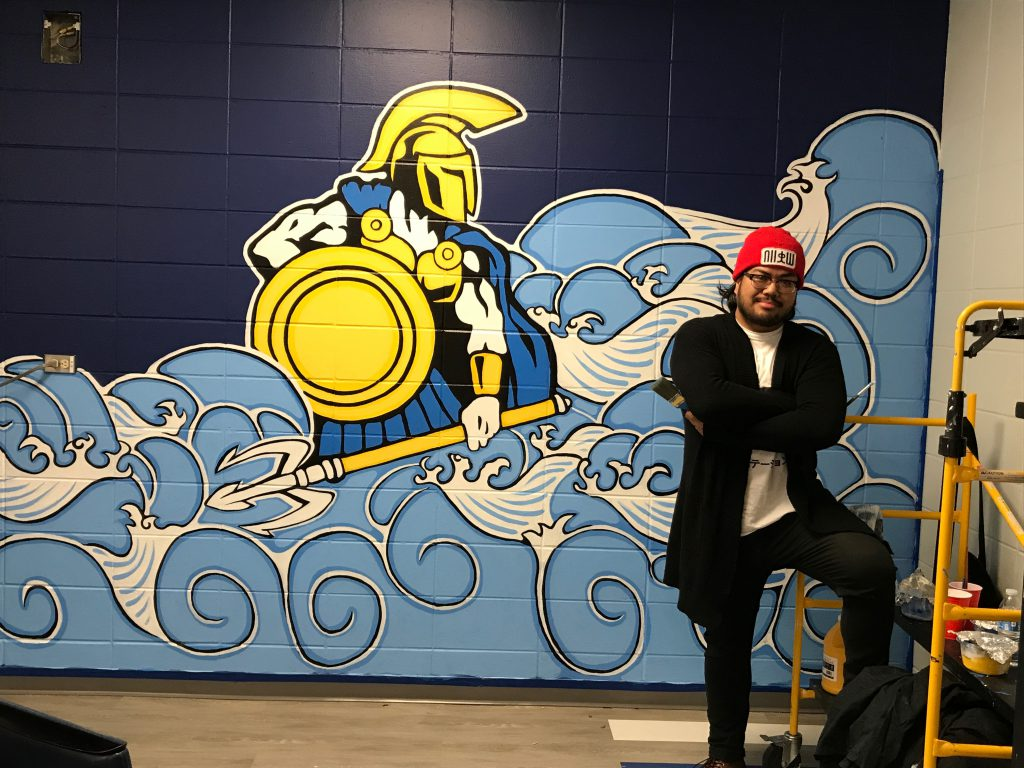 A man stands in front of a mural of the St. Petersburg College mascot he painted on a wall at the Clearwater Campus.