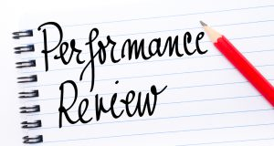 "Illustration of a pencil writing the words ""performance review"""