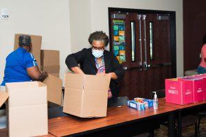 SPC employee packs food box