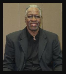 Minson Rubin, in black suit, smiles into the camera.