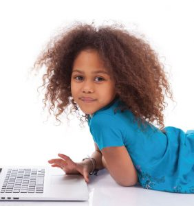 Little girl in blue shirt lies on her stomach in front of an open laptop.