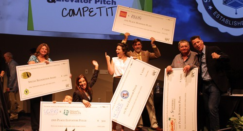 2014 Annual Business Plan and Elevator Pitch Competition winners standing on stage holding checks.