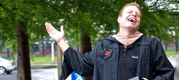 Business Administration Alumnus in graduation robe holding cap, standing outside under a tree laughing
