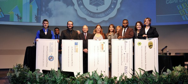 Business Competition winners up on stage holding checks