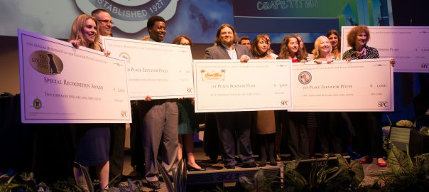 Future Entrepreneurs at the 7th Annual Business Plan and Elevator Pitch Competition standing on stage holding up checks