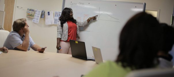 Woman pointing to graph on dry erase board at Business Expo