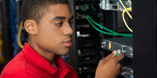Photo of man plugging network cable into a switch