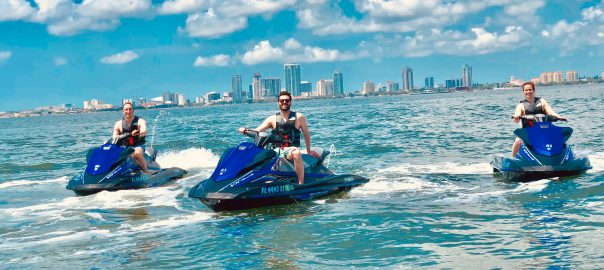 Three people sit on jet skis in the middle of Tampa Bay.