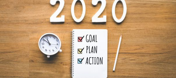 "A journal reading ""goal, plan, action"" next to a clock."