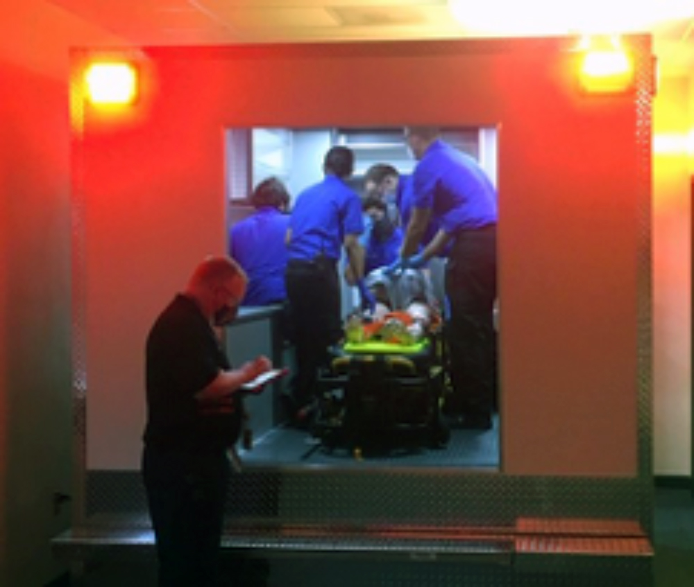EMS students in blue uniforms receive hands-on training inside of the ambulance simulation while an instructors stands outside of it overseeing their work