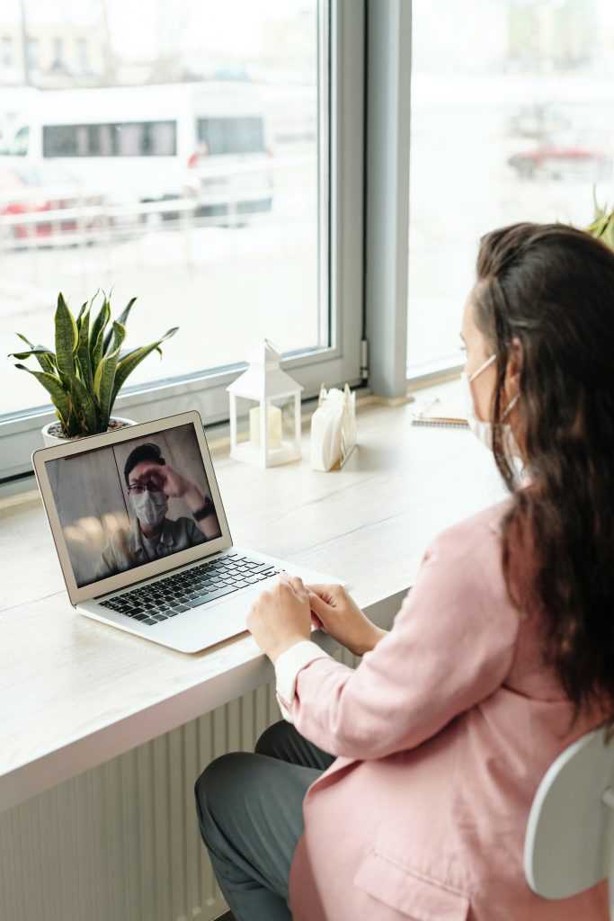 Young woman in a pink jacket video chatting with a young man on a laptop.