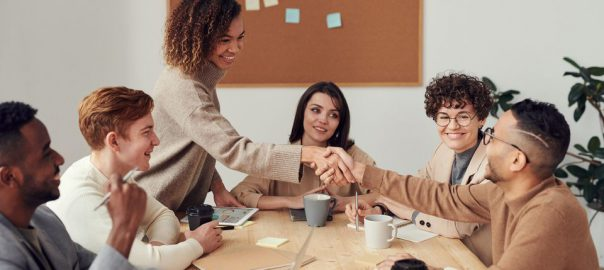 Group of colleagues shaking hands with one another and smiling in a conference room.