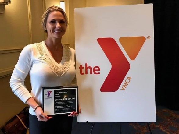 Headshot image of Stephanie Dushane holding 10 year recognition plaque in front of the Ymca sign.