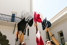students holding up their graduation caps outdoors at a school