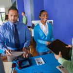 Hispanic Man standing next to African American woman greeting a man holding a professional portfolio.