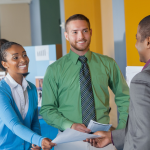 Two students in business attire talk to a prospective employer at a career fair.