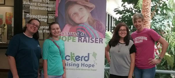Four women standing in front of poster for Eckerd Kids - Raising Hope Program with Women on the Way