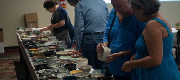 People look at a table of bowls to pick out a bowl for their soup and to take home with them.