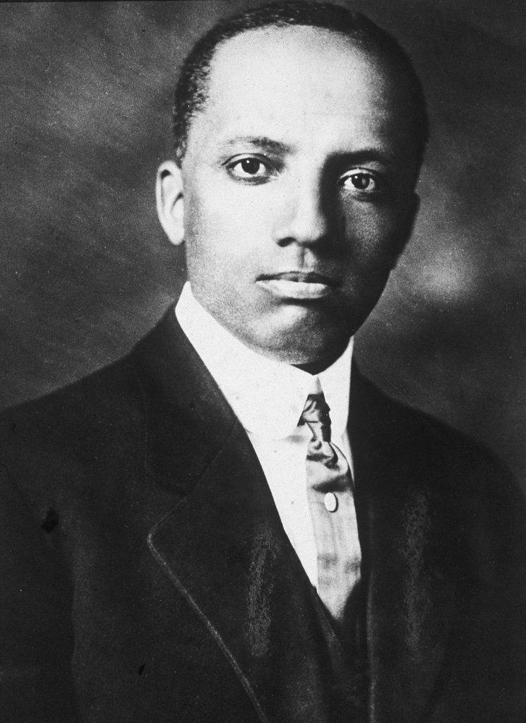 Dr. Carter G. Woodson dressed in a suit and tie.