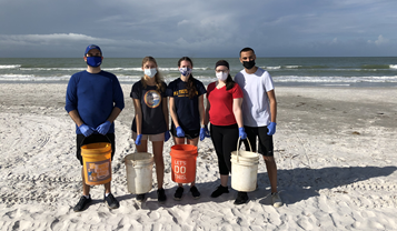 Five students stand on a beach holding clean-up buckets.