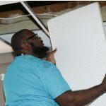 man replacing ceiling tile
