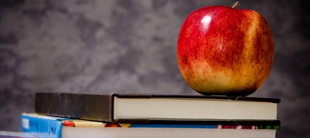 An apple sitting on top of books.