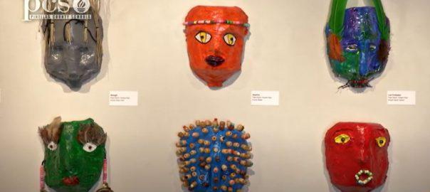 two rows of masks hang at art display