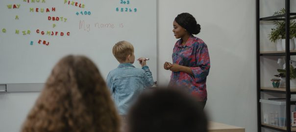 teacher assists student at whiteboard