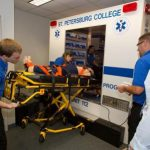 Paramedic students loading a patient into the simbulance