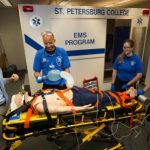 EMS Instructor Ralph Sibbio working with medic students outside the simbulance