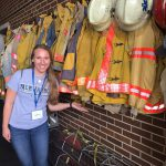 Student standing in front of fire fighter jackets