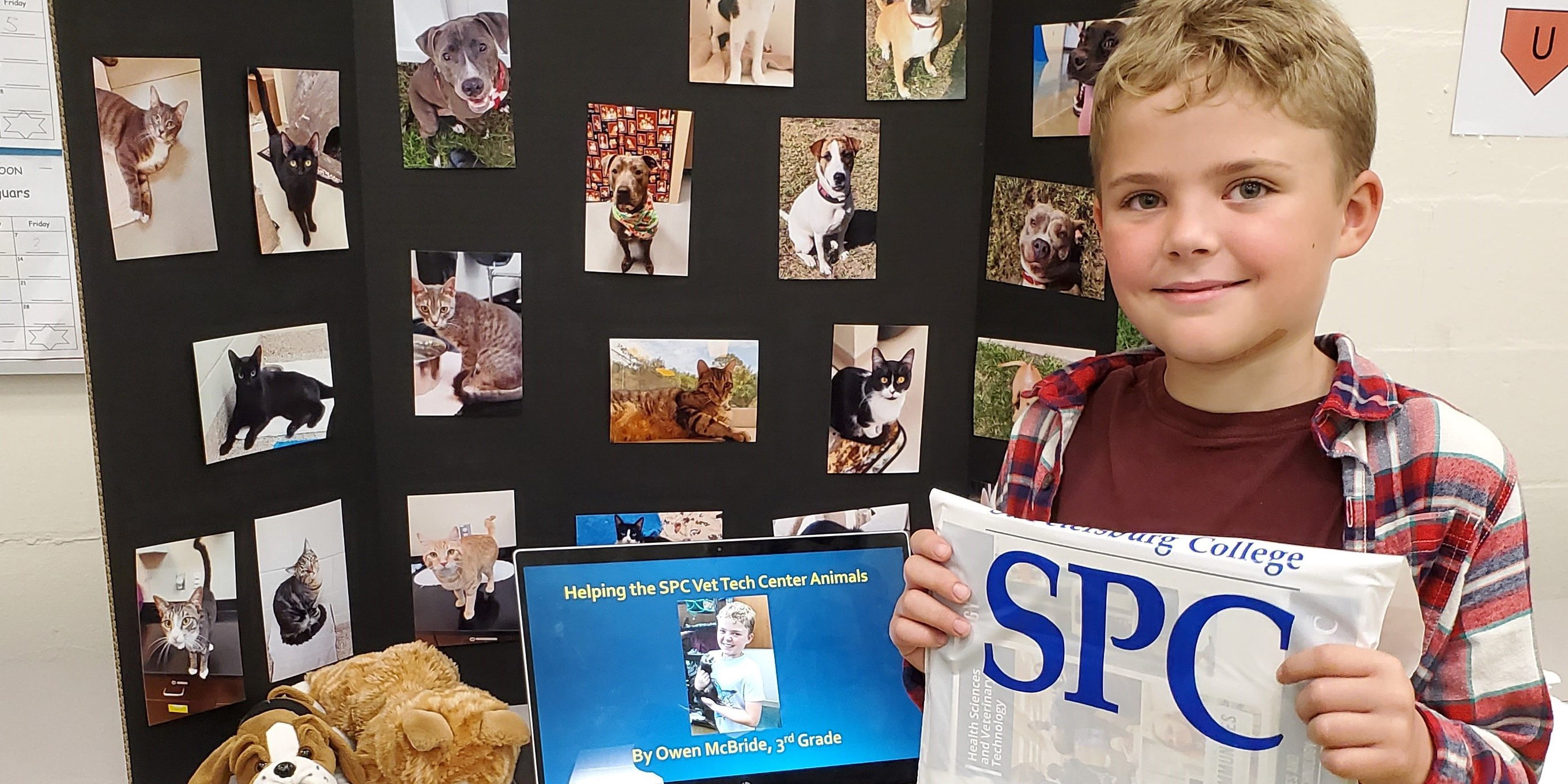 A small blonde boy holds an SPC bag in front of a presentation covered in pictures of animals up for adoption.