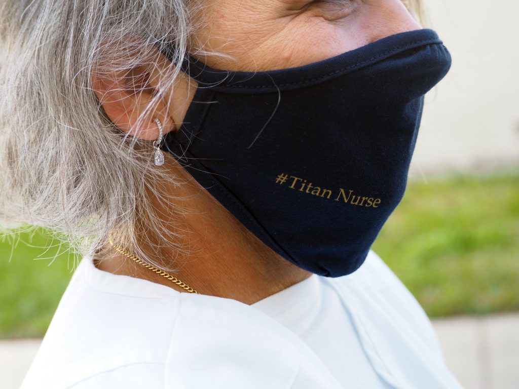 Close up of a nursing student's dark blue mask that reads hashtag Titan Nurse on it in gold lettering.