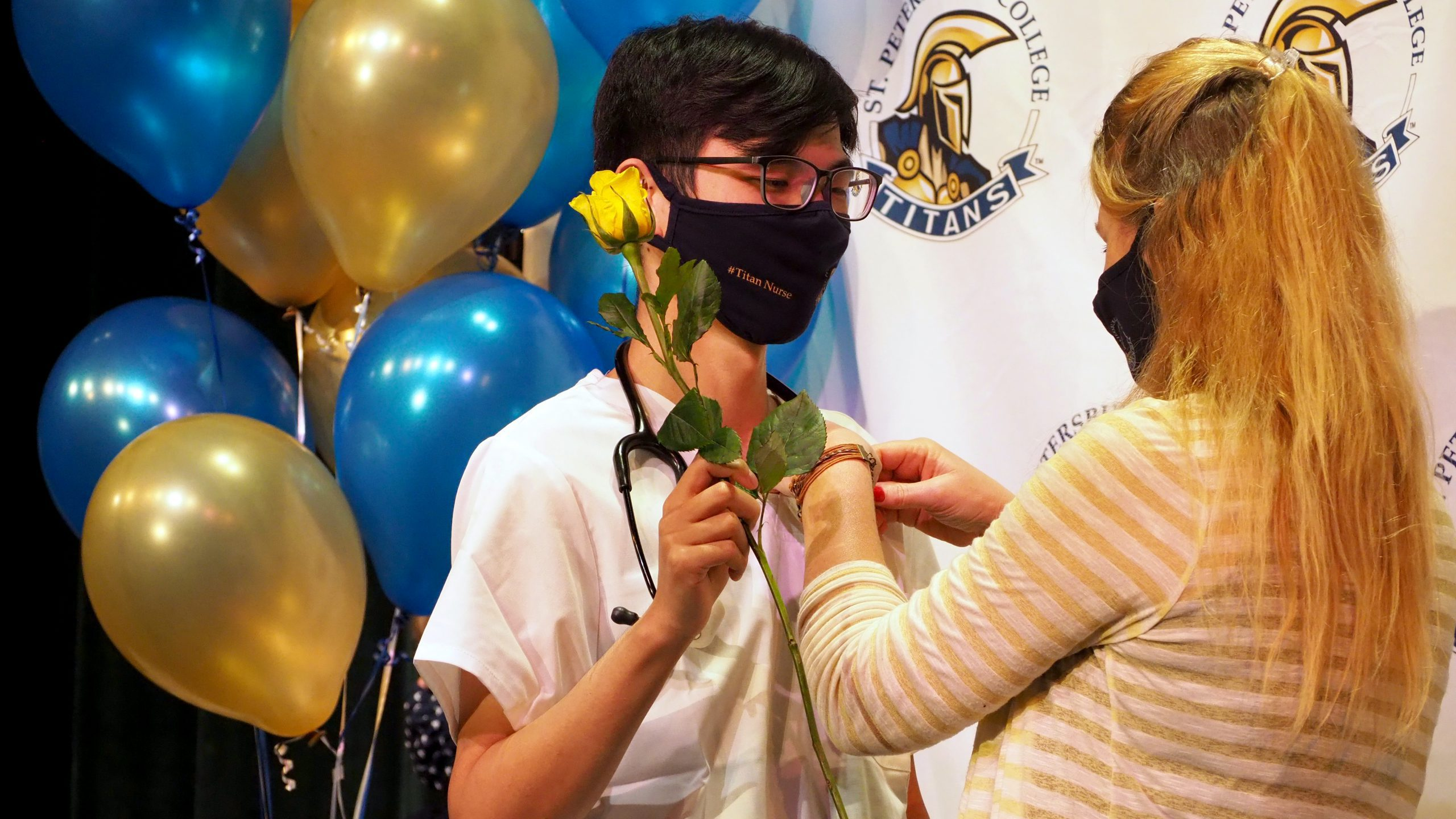 A male nursing student receives his nursing pin while holding a yellow rose.