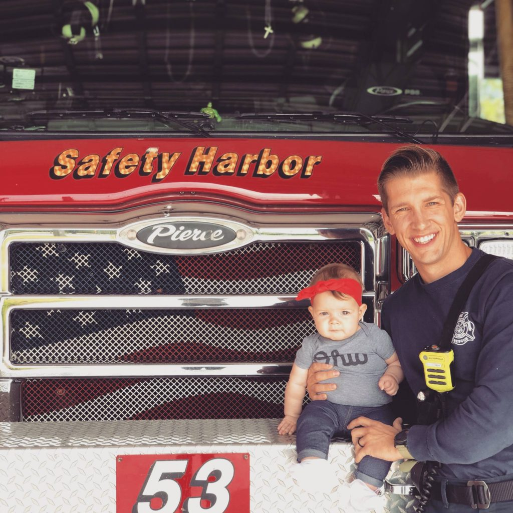 A firefighter sitting in front of a fire engine holding a baby.