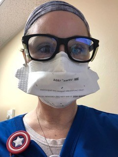 A woman in blue scrubs wearing glasses and a face mask.