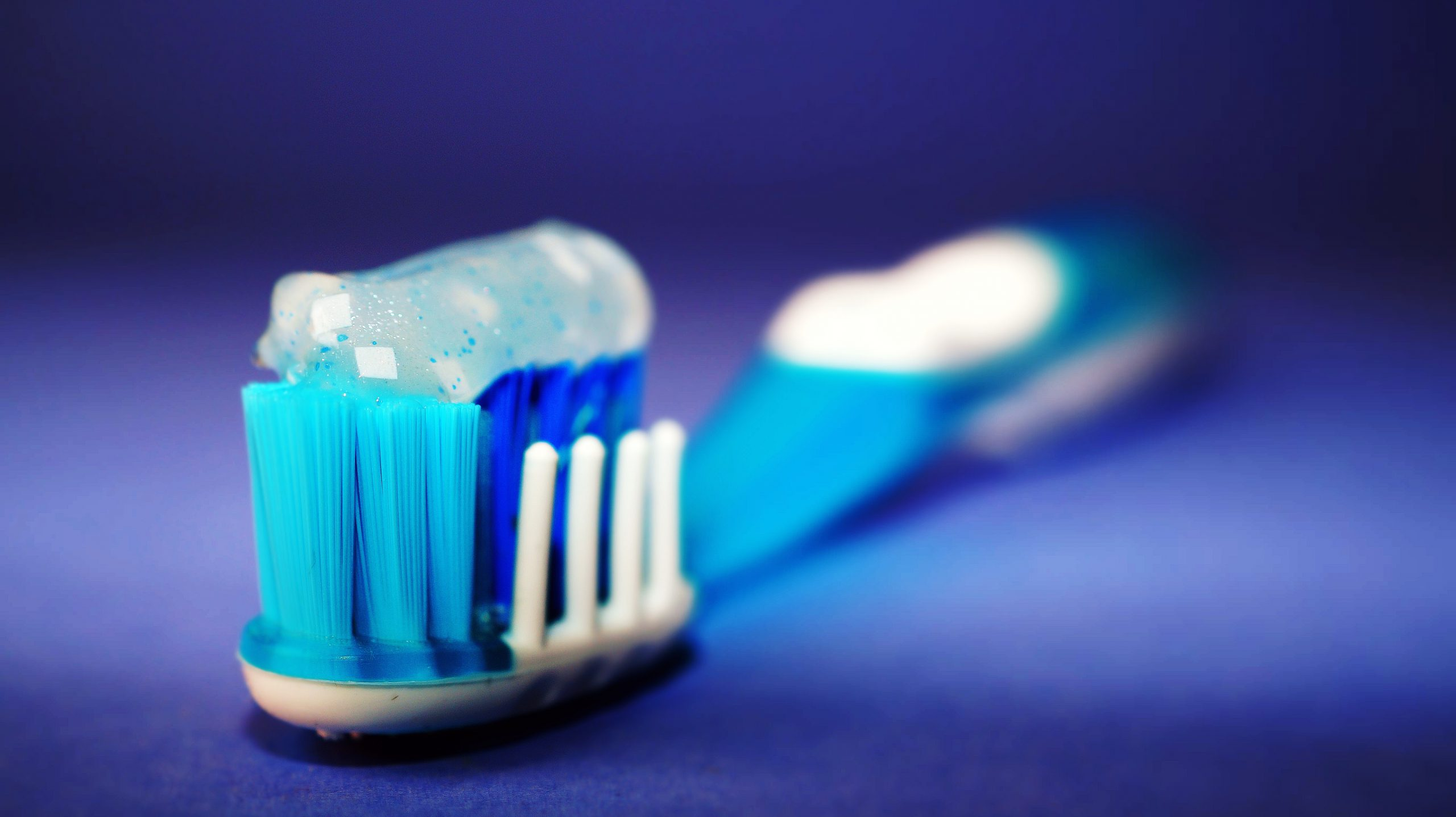 Close up shot of a blue toothbrush that has sparkly light blue toothpaste along its bristles.