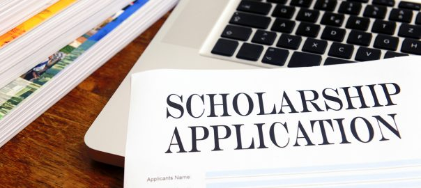 blank scholarship  application on desktop with books and laptop