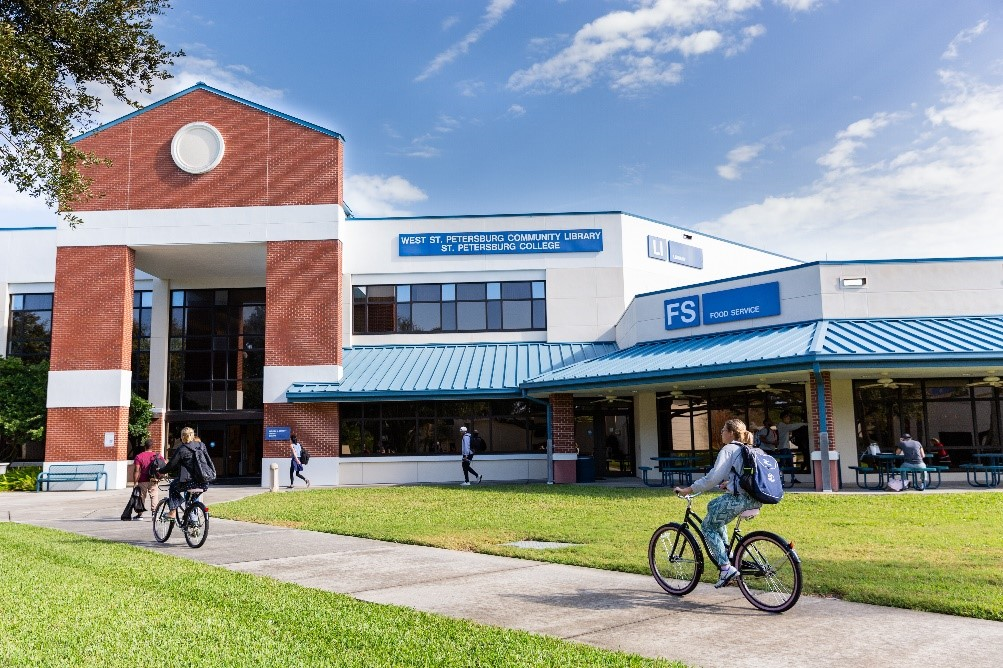 A photo of the St. Pete / Gibbs Campus with students cycling across Campus.