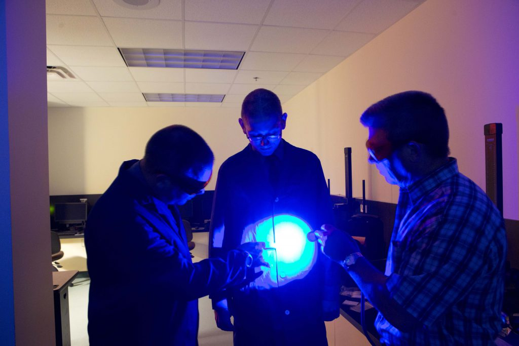 A photo of three individuals, two students around a centered professor. The students are looking over the professor's clothing with blue lights to detect any indication of crime.