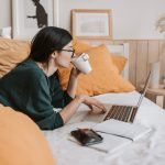 woman works from computer in bed while drinking from a mug